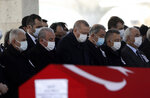 Turkey's President Recep Tayyip Erdogan, center left, prays as Turkish leaders, army commanders, family members and colleagues attend funeral prayers and a ceremony for 11 military personnel, including a high-ranking officer, at Ahmet Hamdi Akseki Mosque, in Ankara, Turkey, Friday, March 5, 2021. Turkish army officers were killed on Thursday when an army helicopter crashed in a snow-covered mountainous area in Bitlis, eastern Turkey. (AP Photo/Burhan Ozbilici)