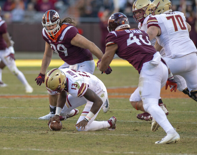 Boston College Anthony Brown quarterback spins and drops a knee under pressure from Virginia Tech's Vinny Mihota, 99, and Emmanuel Belmar, 40,  during the first half of an NCAA college football game in Blacksburg, Va., Saturday, Nov. 3, 2018. (AP Photo/Matt Bell)