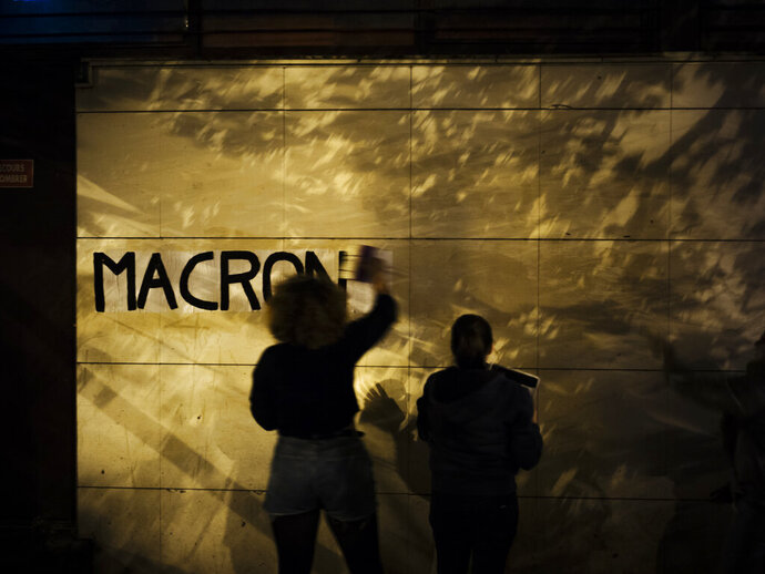 In this Oct. 24 2019, photo, Maya, 19, a student from Versailles pastes a slogan with the name of French President Emmanuel Macron in the evening in the south of Paris. France, a country that has prided itself on gender equality, is beginning to pay serious attention to its yet-intractable problem of domestic violence. Under cover of night, activists have glued slogans to the walls to draw attention to domestic violence, a problem French President Emmanuel Macron has called