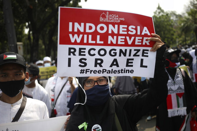 A Muslim woman holds up a poster during a rally against Israel's attacks on Gaza, outside the U.S. Embassy in Jakarta, Indonesia, Friday, May 21, 2021. (AP Photo/Dita Alangkara)