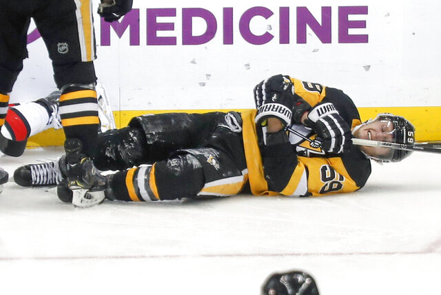 Pittsburgh Penguins' Jake Guentzel (59) rolls on the ice after being injured after scoring a goal against the Ottawa Senators during the third period of an NHL hockey game, Monday, Dec. 30, 2019, in Pittsburgh. Guentzel left the ice and did not return to the game. (AP Photo/Keith Srakocic)