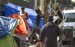 A homeless woman throws a plastic chair in the air downtown Los Angeles Tuesday, Sept. 17, 2019. Los Angeles Mayor Eric Garcetti says he hopes President Donald Trump will work with the city to end homelessness as the president visits California for a series of fundraisers. Garcetti says the federal government could aid Los Angeles with surplus property or money to create additional shelters. Garcetti says he has not been invited to meet with the president. in Los Angeles (AP Photo/Damian Dovarganes)