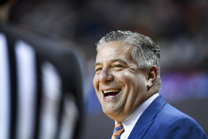 Auburn head coach Bruce Pearl smiles at an official during the first half of an NCAA college basketball game against Tennessee Saturday, Feb. 22, 2020, in Auburn, Ala. (AP Photo/Julie Bennett)