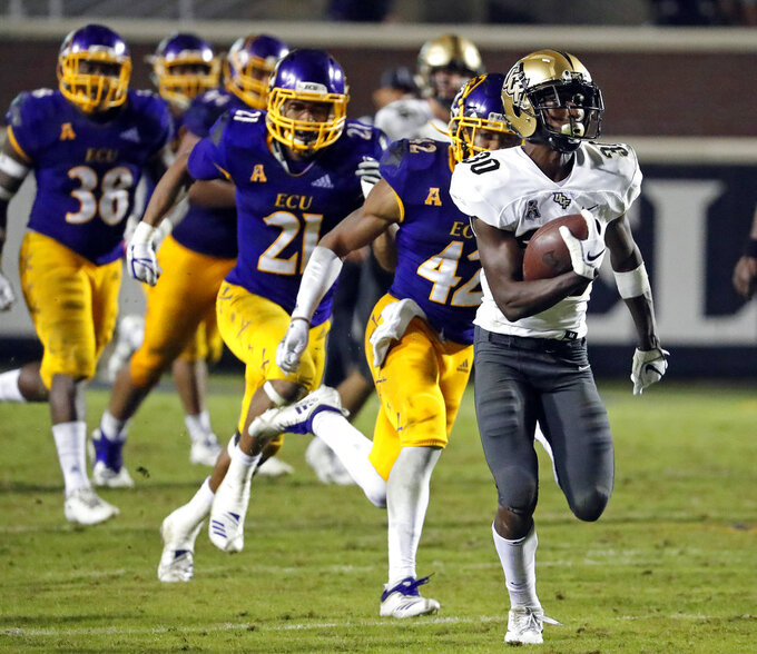 Central Florida's Greg McCrae (30) runs the ball for a touchdown with the East Carolina defense in pursuit during the second half of an NCAA college football game in Greenville, N.C., Saturday, Oct. 20, 2018. UCF won 37-10. (AP Photo/Karl B DeBlaker)
