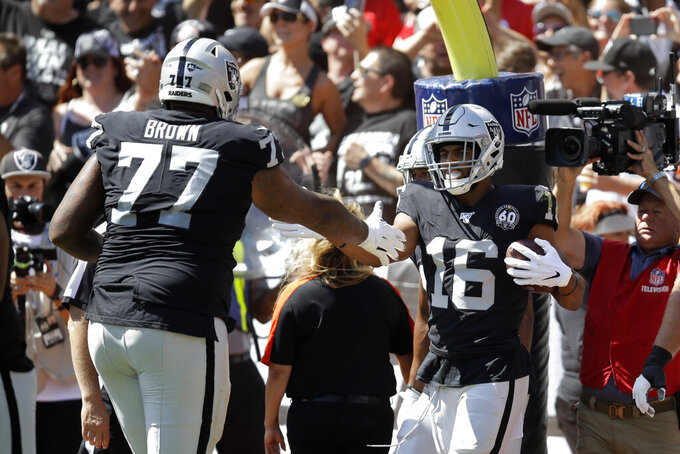 Oakland Raiders wide receiver Tyrell Williams (16) is greeted by offensive tackle Trent Brown (77) after scoring a touchdown during the first half of an NFL football game against the Kansas City Chiefs Sunday, Sept. 15, 2019, in Oakland, Calif. (AP Photo/Ben Margot)