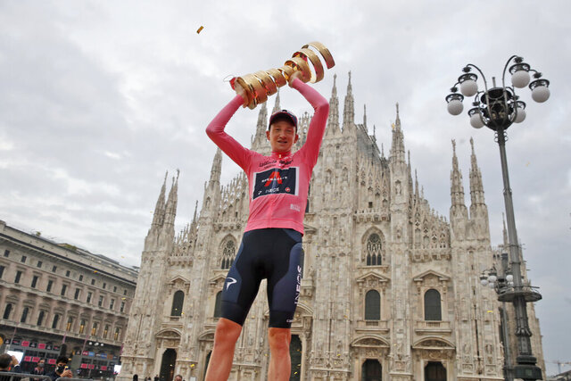 Britain's Tao Geoghegan Hart, framed by the gothic cathedral, holds up the trophy after winning the Giro d'Italia cycling race, in Milan, Italy, Sunday, Oct. 25, 2020. (AP Photo/Luca Bruno)