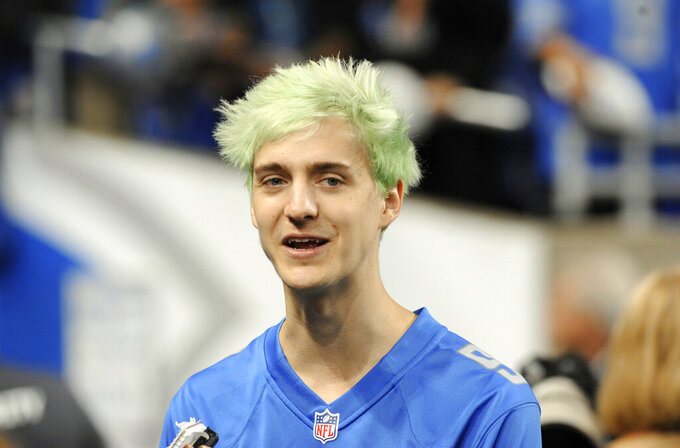 "FILE - In this Sept. 10, 2018, file photo, Fortnite superstar Tyler ""Ninja"" Blevins watches before an NFL football game between the Detroit Lions and New York Jets in Detroit. Blevins is leaving Twitch and taking his video game live streams to Microsoft's Mixer platform, a stunning transition that could have wide-ranging consequences for the rapidly growing industry. Blevins announced his move Thursday, Aug. 1, 2019,  ending a hugely profitable partnership with Twitch, a live streaming giant owned by Amazon. (AP Photo/Jose Juarez, File)"