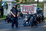 FILE - In this July 27, 2020, file photo, a California Highway Patrol officer inspects a chained protester who was part of a group calling for mass prison inmate releases outside of California Gov. Gavin Newsom's mansion in Fair Oaks, Calif. California state prison officials say in a recent court filing that as many as 17,600 inmates are eligible for release due to the coronavirus, 70% more than previously estimated and a total that victims and police say includes dangerous criminals who should stay locked up.  (Daniel Kim/The Sacramento Bee via AP, File)