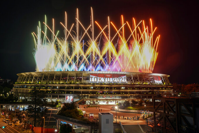 """FILE - In this Aug. 8, 2021, file photo, fireworks illuminate over National Stadium during the closing ceremony of the 2020 Tokyo Olympics, in Tokyo. When the Tokyo Olympics began during a worsening pandemic, the majority of the host nation was in opposition, with Emperor Naruhito dropping the word """"celebrating"""" from his opening declaration of welcome. But once the Games got underway and local media switched to covering Japanese athletes' """"medal rush,"""" many were won over. (AP Photo/Kiichiro Sato, File)"""