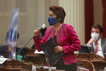 Observing coronavirus precautions, Sen. Anna Caballero, D-Salinas, wears a face mask and stands behind plexiglass, as she discusses her opposition to a natural resources trailer bill before the Senate at the Capitol, in Sacramento, Calif., Thursday, June 25, 2020. Caballero opposed the measure saying it would hurt one of the water agencies in her district. The bill, one of the more than one dozen budget trailer bills before the Senate, was approved. (AP Photo/Rich Pedroncelli)