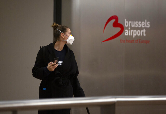 A woman wears a protective mask as she arrives at Brussels International Airport in Brussels, Friday, March 13, 2020. European Union interior ministers on Friday were trying to coordinate their response to the COVID-19 coronavirus as the number of cases spreads throughout the 27-nation bloc and countries take individual measures to slow the disease down. For most people, the new coronavirus causes only mild or moderate symptoms, such as fever and cough. For some, especially older adults and people with existing health problems, it can cause more severe illness, including pneumonia. (AP Photo/Virginia Mayo)