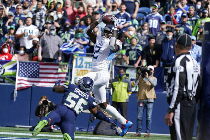 Tennessee Titans wide receiver Julio Jones (2) makes a catch in the end zone above Seattle Seahawks linebacker Jordyn Brooks (56), but came down with one foot out of bounds during the first half of an NFL football game, Sunday, Sept. 19, 2021, in Seattle. (AP Photo/Elaine Thompson)