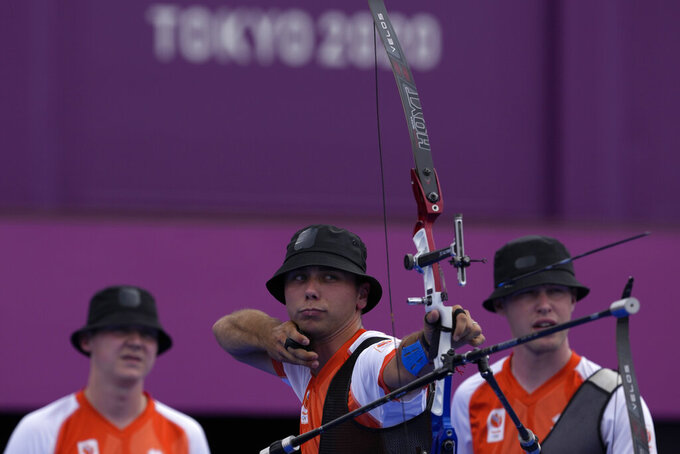 Netherlands' Steve Wijler, center, shoots the arrow flanked by teammates Gijs Broeksma, right, and Sjef Van den Berg during the men's team competition at the 2020 Summer Olympics, Monday, July 26, 2021, in Tokyo, Japan. (AP Photo/Alessandra Tarantino)