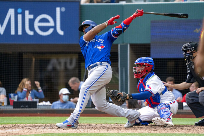 Toronto Blue Jays' Teoscar Hernandez follows through on a ground ball that scored Cavan Biggio on an error by Texas Rangers shortstop Charlie Culberson during the seventh inning of a baseball game Monday, April 5, 2021, in Arlington, Texas.  (AP Photo/Jeffrey McWhorter)