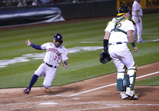 Houston Astros' Jose Altuve (27) slides into home plate past Oakland Athletics catcher Sean Murphy (12) to score a run during the fourth inning of an opening day baseball game Oakland, Calif., Thursday, April 1, 2021. (AP Photo/Tony Avelar)