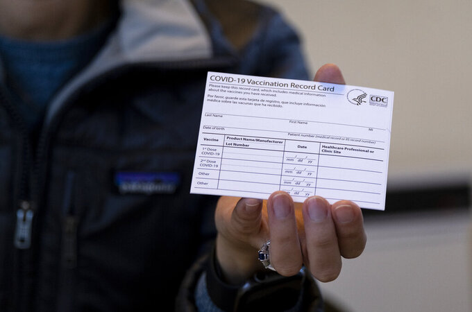 FILE - In this Jan. 10, 2021 file photo, Sarah Gonzalez of New York, a Nurse Practitioner, displays a COVID-19 vaccine card at a New York Health and Hospitals vaccine clinic in the Brooklyn borough of New York.  Workers in New York City-run hospitals and health clinics will have to get vaccinated or get tested weekly under a policy announced Wednesday, July 21,  to battle a rise in COVID-19 cases fueled by the highly contagious delta variant. (AP Photo/Craig Ruttle, File)