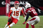 Kansas City Chiefs quarterback Patrick Mahomes (15) tries to elude Arizona Cardinals cornerback Malcolm Butler (21) during the first half of an NFL football game, Friday, Aug. 20, 2021, in Glendale, Ariz. (AP Photo/Rick Scuteri)
