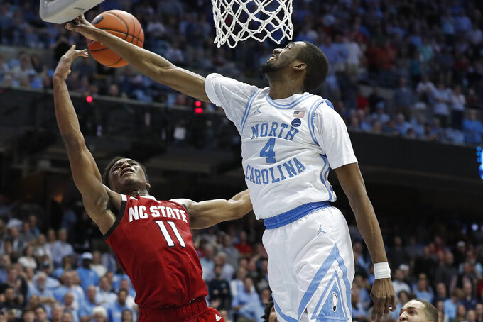North Carolina guard Brandon Robinson (4) blocks North Carolina State guard Markell Johnson (11) during the second half of an NCAA college basketball game in Chapel Hill, N.C., Tuesday, Feb. 25, 2020. (AP Photo/Gerry Broome)