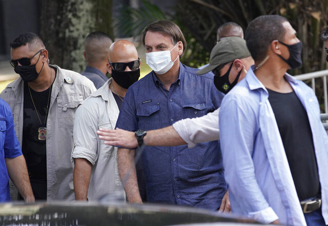 Surrounded by federal police officers, Brazil's President Jair Bolsonaro, center, leaves a polling station after voting in municipal elections in Rio de Janeiro, Brazil, Sunday, Nov. 15, 2020.  (AP Photo/Ricardo Borges)