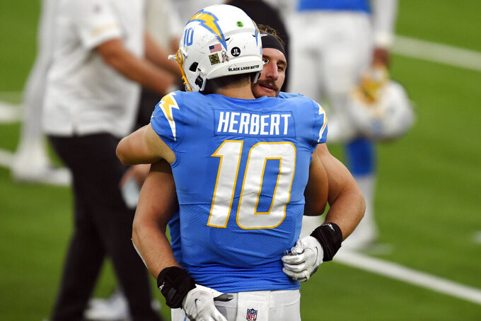 Los Angeles Chargers quarterback Justin Herbert (10) hugs teammate Joey Bosa after a win over the New York Jets during an NFL football game Sunday, Nov. 22, 2020, in Inglewood, Calif. (AP Photo/Kyusung Gong)