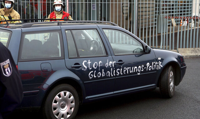 A car stand in front of the chancellery after it crashed into the front gate of the building housing German Chancellors Angela Merkel's offices in Berlin, Germany, Wednesday, Nov. 25, 2020. Slogan reads 'stop the globalization policies'. (AP Photo/Michael Sohn)