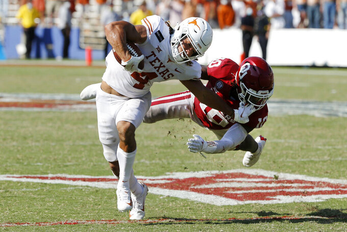 Texas wide receiver Jordan Whittington (4) tries to break a tackle from Oklahoma defensive back Pat Fields (10) during overtime of an NCAA college football game in Dallas, Saturday, Oct. 10, 2020. Oklahoma defeated Texas 53-45 in four overtimes.(AP Photo/Michael Ainsworth)