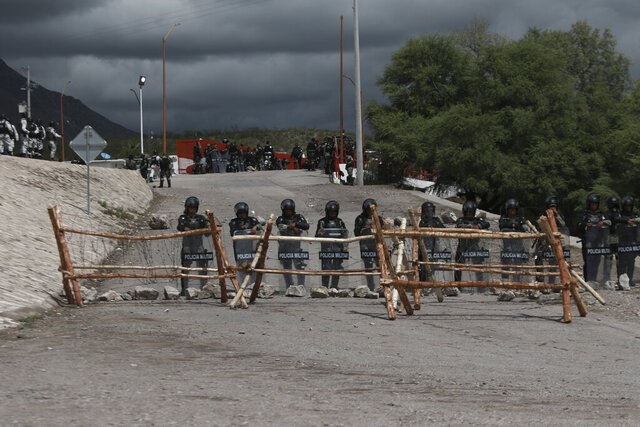 National Guard troops equipped with riot gear stand guard at Las Pilas dam, two days after withdrawing from nearby La Boquilla dam after clashing with hundreds of farmers, in Camargo, Chihuahua State, Mexico, Thursday, Sept. 10, 2020. President Andrés Manuel López Obrador said Thursday he regretted the killing of a woman and the wounding of her husband following a Tuesday clash between National Guard troops and farmers over water. (AP Photo Christian Chavez)