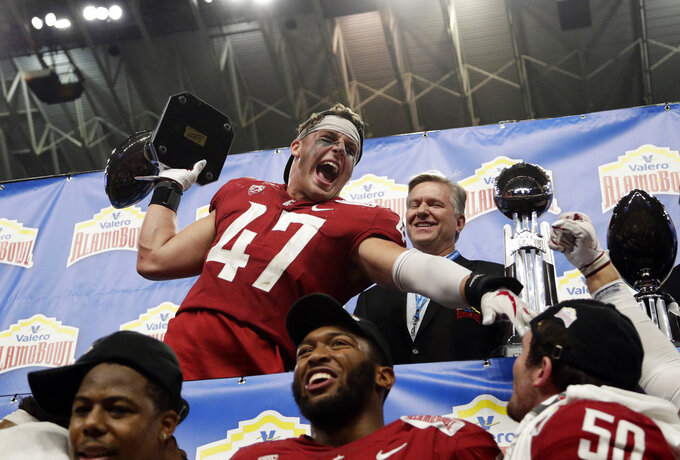 Washington State linebacker Peyton Pelluer (47) holds his Defensive Player of the Game trophy as he celebrates the team's 28-26 win over Iowa State in the Alamo Bowl NCAA college football game, Friday, Dec. 28, 2018, in San Antonio. (AP Photo/Eric Gay)
