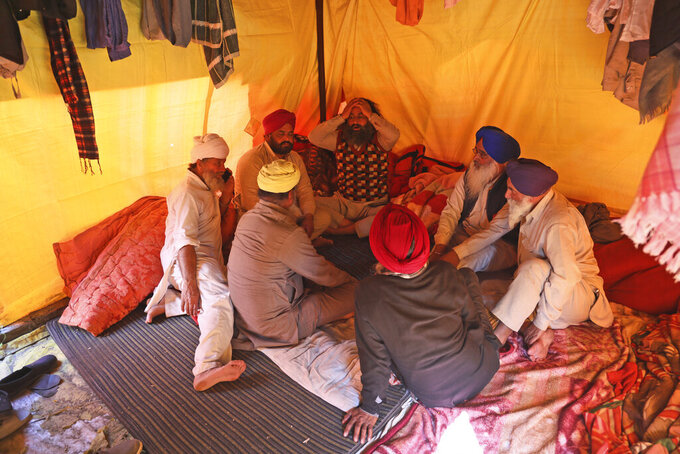 Sikh farmers sit inside their makeshift tent at Singhu, the Delhi-Haryana border camp for protesting farmers against three farm bills, in New Delhi, India, Wednesday, Jan. 27, 2021. Leaders of a protest movement sought Wednesday to distance themselves from a day of violence when thousands of farmers stormed India's historic Red Fort, the most dramatic moment in two months of demonstrations that have grown into a major challenge of Prime Minister Narendra Modi's government. (AP Photo/Manish Swarup)