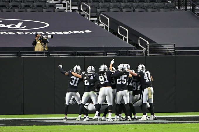 Las Vegas Raiders players celebrate after strong safety Jeff Heath made an interception against the Denver Broncos during the first half of an NFL football game, Sunday, Nov. 15, 2020, in Las Vegas. (AP Photo/David Becker)