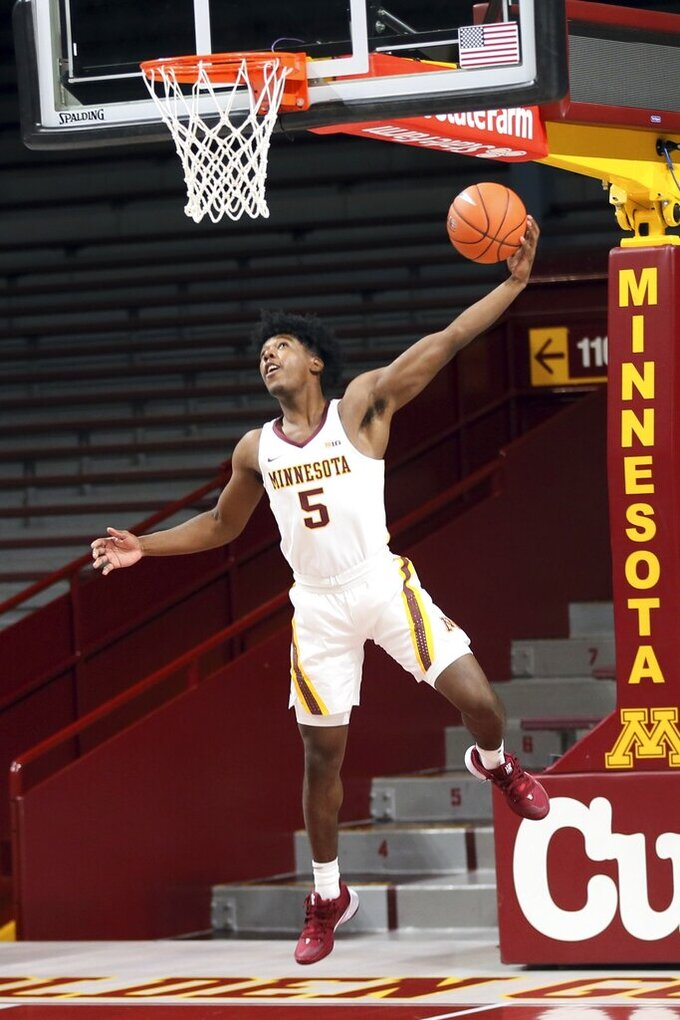Minnesota's Marcus Carr eyes the basket as he poses for a photo during NCAA college basketball media day Friday, Oct. 18, 2019, in Minneapolis. (AP Photo/Jim Mone)
