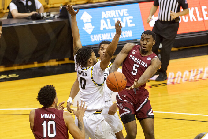 South Carolina's Jermaine Couisnard, right, passes the ball around Missouri's Torrence Watson, center, to Justin Minaya, left, during the first half of an NCAA college basketball game Tuesday, Jan. 19, 2021, in Columbia, Mo. (AP Photo/L.G. Patterson)