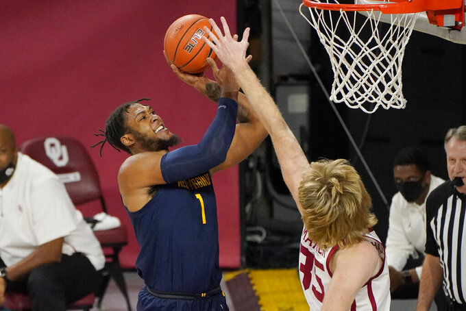 West Virginia forward Derek Culver (1) shoots as Oklahoma forward Brady Manek (35) defends in the first half of an NCAA college basketball game Saturday, Jan. 2, 2021, in Norman, Okla. (AP Photo/Sue Ogrocki)