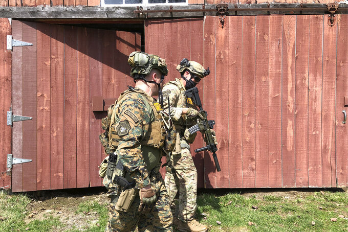 Members of the Vermont State Police tactical team search a barn for 51-year-old Harley Breer, who allegedly assaulted a neighbor in Marshfield last week, in Marshfield, Vt., Sunday, April 11, 2021. Breer has a criminal history including convictions for kidnapping and aggravated domestic assault, authorities said. (AP Photo/Lisa Rathke)