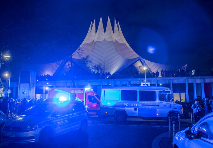 Police and emergency cars stand in front of the Tempodrom venue after a shooting in Berlin, Germany, early Saturday, Feb. 15, 2020. According to police one person was killed. (Paul Zinken/dpa via AP)