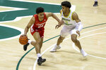 Houston's Quentin Grimes, left, drives past South Florida's David Collins during the first half of an NCAA college basketball game Wednesday, Feb. 10, 2021, in Tampa, Fla. (AP Photo/Mike Carlson)