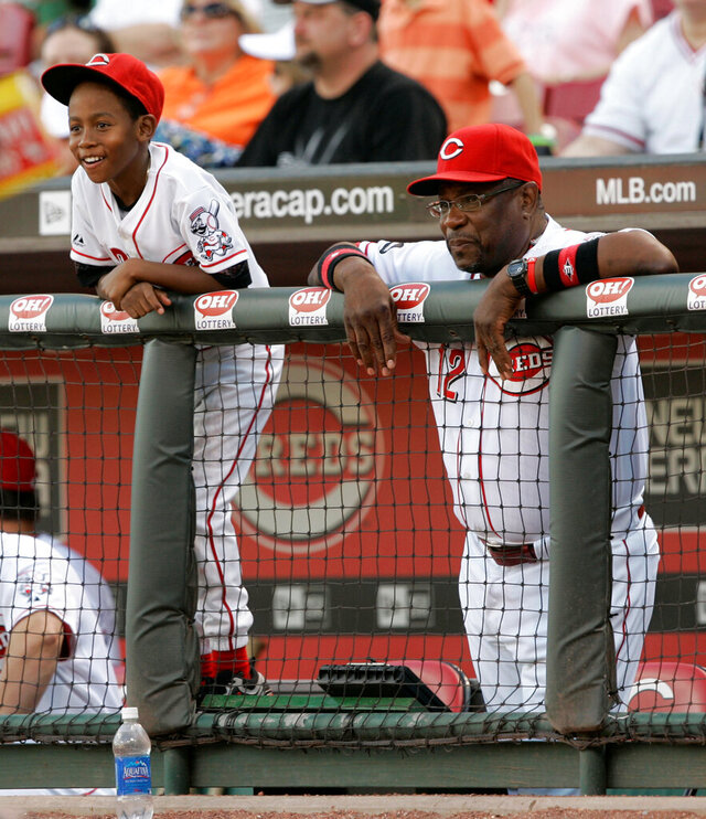 FILE - In this Aug. 7, 2008, file photo, Cincinnati Reds manager Dusty Baker, left, watches a baseball game against the Houston Astros in the dugout with son Darren in Cincinnati. Darren Baker considers his father the perfect person to take over the Houston Astros, and the college second baseman insists that's from a baseball player perspective not just as a proud son.