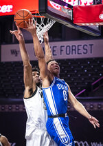 Duke forward Wendell Moore Jr. (0) shoots as Wake Forest center Emmanuel Okpomo (30) defends during an NCAA college basketball game Wednesday, Feb. 17, 2021, in Wintson-Salem, N.C. (Andrew Dye/The Winston-Salem Journal via AP, Pool)