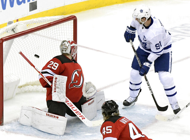 Toronto Maple Leafs center John Tavares (91) scores a goal past New Jersey Devils goaltender Mackenzie Blackwood (29) during the third period of an NHL hockey game Friday, Dec. 27, 2019, in Newark, N.J. (AP Photo/Bill Kostroun)