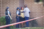 A woman cries as she tries to cross police tape at the scene of a shooting outside a home in Chicago.   Police say an argument at a house on Chicago's South Side erupted in fatal gunfire, leaving some dead and others injured. (Ashlee Rezin Garcia /Chicago Sun-Times via AP)