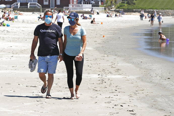 A couple wear a protective masks due to the COVID-19 virus outbreak as they walk on the shore of Good Harbor Beach in Gloucester, Mass., Friday, May 22, 2020. Beaches in Gloucester reopened with restrictions on Friday after being closed two months ago due to the pandemic. (AP Photo/Charles Krupa)