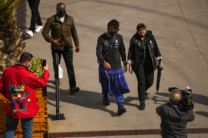 Mercedes driver Lewis Hamilton, center, of Britain walks at the paddock ahead of Sunday's Formula One Turkish Grand Prix at the Intercity Istanbul Park track, outside Istanbul, Turkey, Thursday, Oct. 7, 2021. (AP Photo/Francisco Seco)