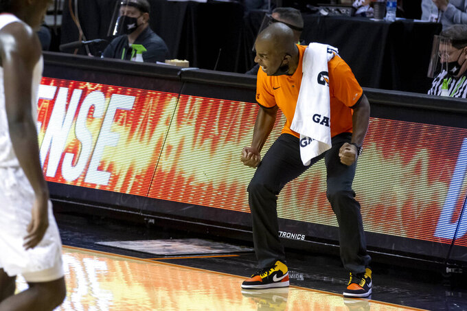 Oklahoma State head coach Mike Boynton Jr. celebrates on the baseline during the first half of an NCAA college basketball game against Oakland in Stillwater, Okla., Saturday, Dec. 5, 2020. (AP Photo/Mitch Alcala)
