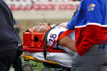 Medical personnel cart Kansas' Taiwan Berryhill (28) off the field during the first half of an NCAA college football game against Texas Tech, Saturday, Dec. 5, 2020, in Lubbock, Texas. (AP Photo/Brad Tollefson)