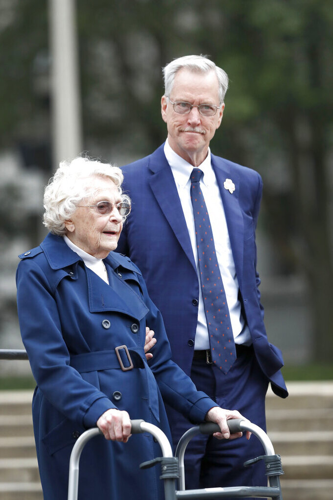 Chicago Bears owner Virginia Halas McCaskey, daughter of Bears' founder George S. Halas, stands with her son, George, before addressing the crowd during a unveiling ceremony outside Soldier Field of statues honoring her father and Walter Payton Tuesday, Sept. 3, 2019, in Chicago. (AP Photo/Charles Rex Arbogast)