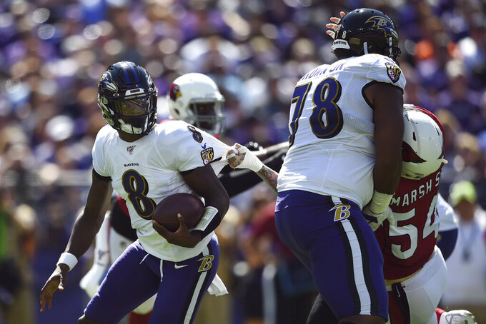 Baltimore Ravens quarterback Lamar Jackson, left, tries to outrun Arizona Cardinals linebacker Cassius Marsh, right, as Marsh is defended by Ravens tackle Orlando Brown in the first half of an NFL football game, Sunday, Sept. 15, 2019, in Baltimore. (AP Photo/Gail Burton)