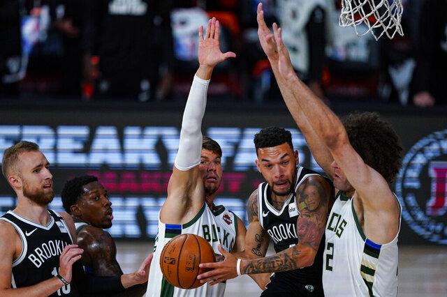 Brooklyn Nets guard Chris Chiozza (4) cuts between Milwaukee Bucks guard Kyle Korver (26) and center Robin Lopez (42) during the first half of an NBA basketball game Tuesday, Aug. 4, 2020 in Lake Buena Vista, Fla. (AP Photo/Ashley Landis)