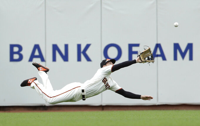 FILE  - In this June 15, 2019, file photo, San Francisco Giants left fielder Mike Yastrzemski dives to catch a fly ball hit by Milwaukee Brewers' Yasmani Grandal for the final out of the ninth inning of a baseball game in San Francisco. (AP Photo/Jeff Chiu, File)