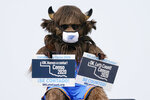 Rumble, the mascot of the Oklahoma City Thunder NBA basketball team, holds signs encouraging participation in the U.S. Census, at a drive-thru Census Mobile Questionnaire Assistance (MQA) event outside the state Capitol in Oklahoma City, Friday, Sept. 18, 2020. (AP Photo/Sue Ogrocki)