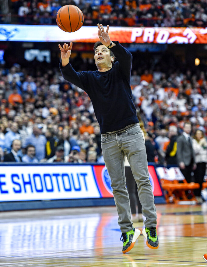 Comedian Jimmy Fallon attempts a three point shot during a timeout in the second half of an NCAA college basketball game between Syracuse and North Carolina in Syracuse, N.Y., Saturday, Feb. 29, 2020. North Carolina defeated Syracuse 92-79. (AP Photo/Adrian Kraus)